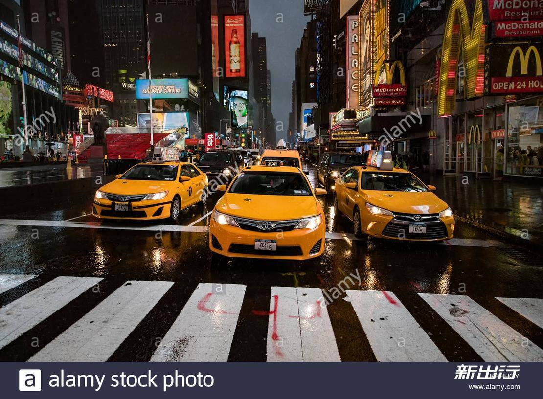 new-york-medallion-yellow-taxi-cabs-line-up-at-crossing-on-a-rainy-KRHHGY.jpg